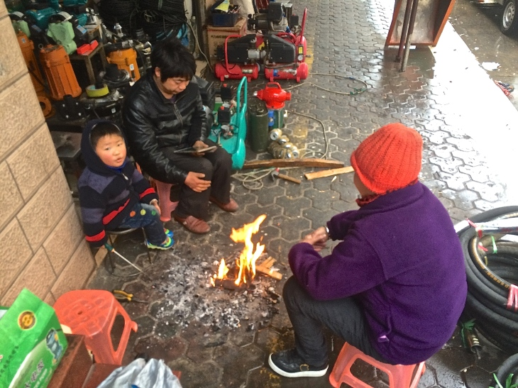 Local shop owners trying to warm up around a sidewalk fire (since it's probably colder inside!)